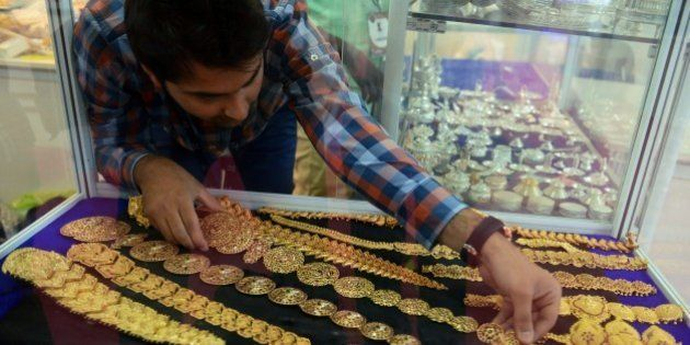 An Indian trader adjusts jewellry displayed during the Hyderabad Jewellery Pearl and Gem Fair (HJF) in...