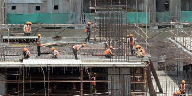 Indian labourers work at the site of an under-construction apartment building in Mumbai on June 1, 2015....