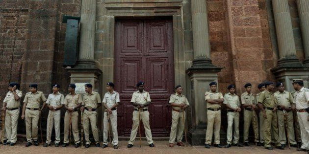 Indian policemen stand guard outside the Basilica of Bom Jesus before the start of a procession carrying...