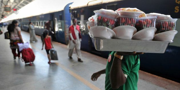 An Indian railway worker carries packaged food at a railway station in Bangalore on February 26, 2013...