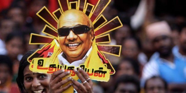 A supporter holds up a cutout with a portrait of Dravida Munnetra Kazhagam (DMK) party chief M. Karunanidhi...