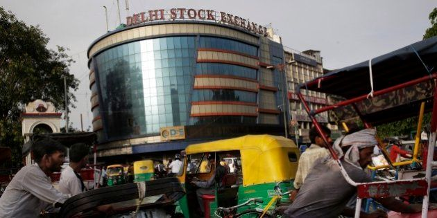 Indian cycle rickshaw pullers await customers outside the Delhi Stock Exchange building in New Delhi,...