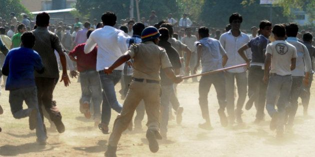 An Indian policeman (C) runs towards a crowd with a lathi stick outside The Vidarbha Cricket Association...