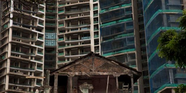 In this Sept. 8, 2014 photo, an Indian man watches from the balcony of a broken house as new high-rise...