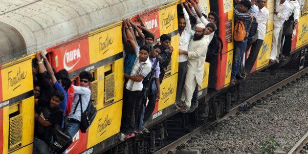 Commuters hang onto an overcrowded suburbun railway train on the Central Railway (CR) line in Mumbai...