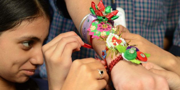 An Indian school girl ties a 'rakhi' - sacred thread - onto the wrist of a school boy on the eve of the...