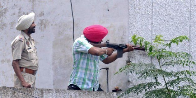 Indian Punjab police personnel fire during an encounter with armed attackers at the police station in...