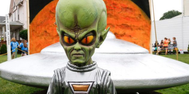 A figure representing a green alien is positioned in front of the permanent flying saucer replica in Mars, Pa. on Friday, June 19, 2015. The small western Pennsylvania town has NASA joining in with a weekend celebration of the Northern Hemisphere Spring Equinox on the planet Mars, marking the start of a new year on the red planet which lasts about 687 Earth days. NASA provided exhibits, booths and outreach activities for the three-day celebration. (AP Photo/Keith Srakocic)