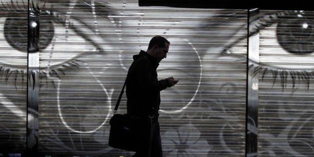 A man looks at his cell phone as he walks on the street in downtown Madrid, Thursday, Oct. 31, 2013....