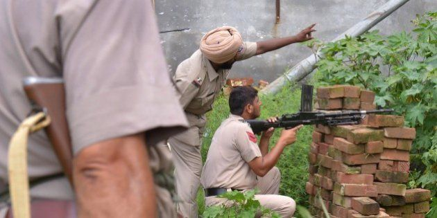 Indian Punjab police personnel take position during an encounter with armed attackers at the police station...