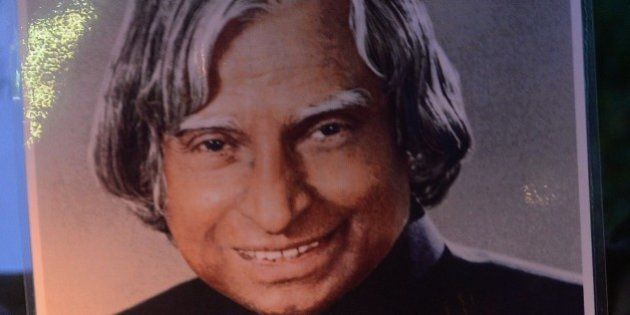 Indian students walk with a photograph of India's former president and top scientist A. P. J. Abdul Kalam...