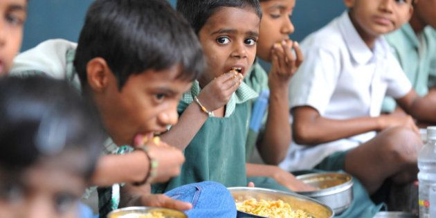 Indian children eat their mid-day meal at an Government High School in Hyderabad, on January 10, 2012....