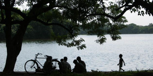 Kolkata, INDIA: Indian men play cards as they sit beside a lake in Kolkata, 31 August 2006. Environmentalists...