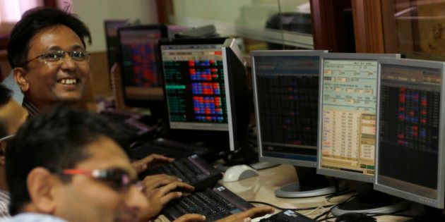 Indian stock brokers react while watching the Bombay Stock Exchange (BSE) index on their trading terminal...