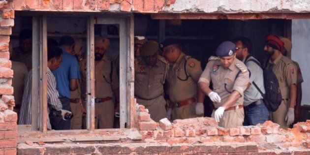 Indian police inspect a the building after armed militants attacked the police station in Dinanagar town,...