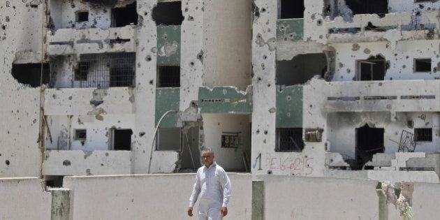 A Libyan man walks past a damaged building in Sirte on July 6, 2012 on the eve of the elections for the...