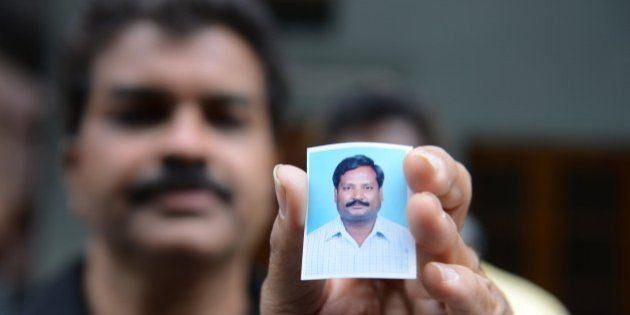 A relative holds up a photograph of Indian national, Balaram, who is thought to have been abducted in...