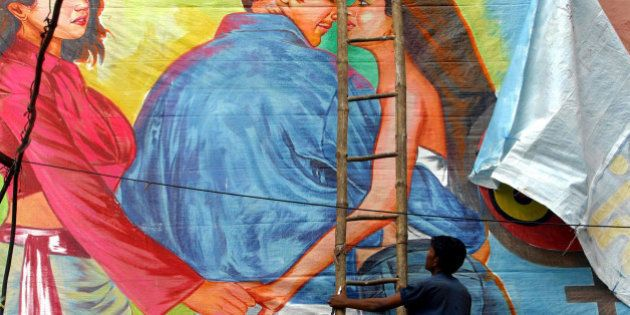 FILE – In this June 15, 2004 file photo, a movie theatre worker removes a poster of Bollywood