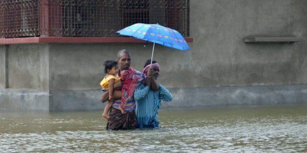 In this photograph taken on August 1, 2015, Indian villagers wade through floodwaters in Bherampur Block,...