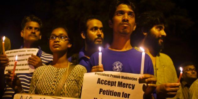 Dozens of Indian activists light candles and hold banners urging the President to stop the scheduled...