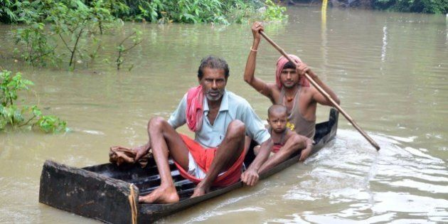 In this photograph taken on August 1, 2015, Indian villagers paddle a small boat through floodwaters...
