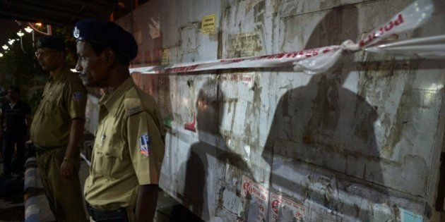 West Bengal state police personel stand guarding the bomb blast spot next to the Central Reserve Police...