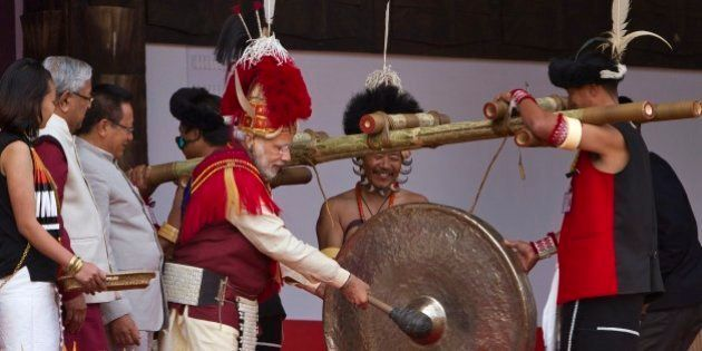 Indian Prime Minister Narendra Modi, third right, dressed in Naga attire hits a traditional musical instrument...