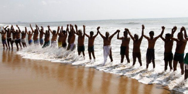 Indian farmers form a human chain on the shore of Bay of Bengal to protest against the ruling Bharatiya...