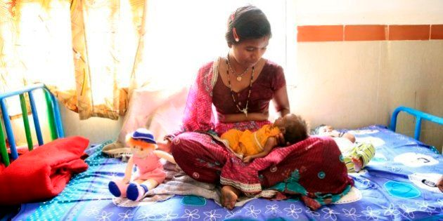 Mum Kali cradles her two-month-old baby daughter at a nutrition rehabilitation centre in Madhya Pradesh,...