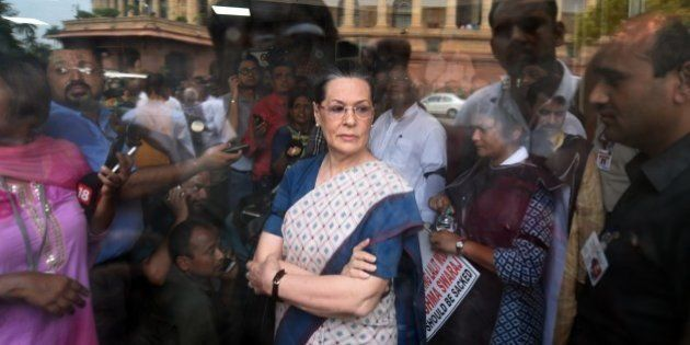 Congress President Sonia Gandhi (C) waits for Vice President Rahul Gandhi and former Prime Minister Manmohan...