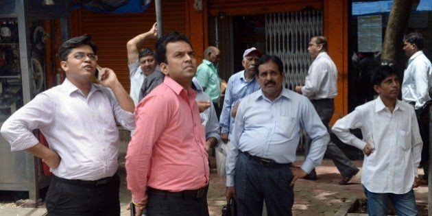 Indian bystanders outside the Bombay Stock Exchange (BSE) watch stock prices on a digital broadcast during...