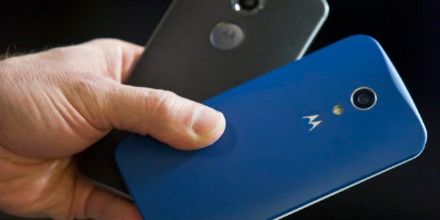 Steve Sinclair, Motorola's vice president of product management, shows the new Moto X, left, and Moto...