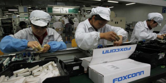 FILE - In this May 26, 2010 file photo, staff members work on the production line at the Foxconn complex...