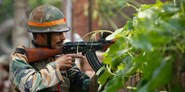 An Indian army soldier holds an AK-47 assault rifle during a fight in the town of Dinanagar, in the northern...