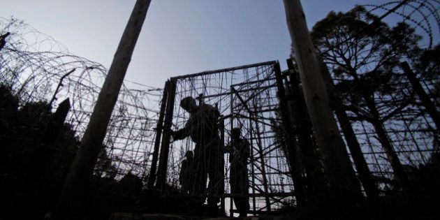 In this Monday, Dec. 23, 2013 photo, Indian army soldiers patrol near the India-Pakistan border fencing...