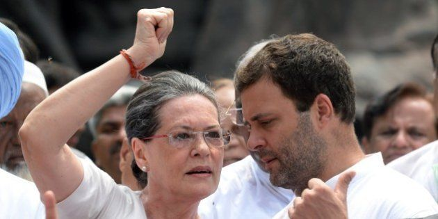 Congress Party President Sonia Gandhi (L) talks with the party vice president and son Rahul Gandhi (R)...