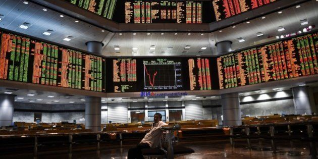 A man sits before electronic boards showing stock movements at the Malaysia Stock Exchange in Kuala Lumpur...