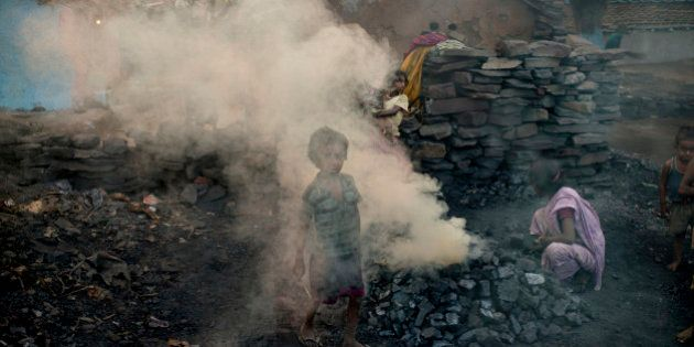 JHARIA, JHARKAND, INDIA - 2014/10/24: A child walks through a cloud of smoke in a village located between...