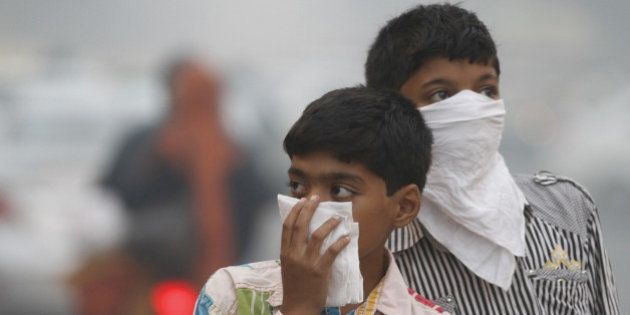 NEW DELHI, INDIA - NOVEMBER 7: Children cover their face to take precaution from the air pollution by...