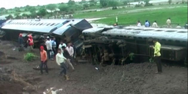 In this image made from video, people gather by the scene where two trains derailed in Harda in Madhya...