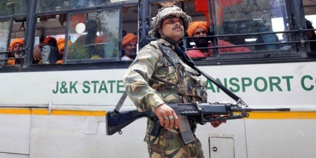 JAMMU, INDIA - AUGUST 5: A CRPF soldier guards the bus carrying passengers of the Amarnath Yatra which...
