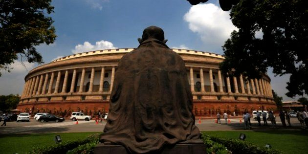 A statue of Mahatma Gandhi overlooks the Indian Parliament house on the opening day of its monsoon session,...