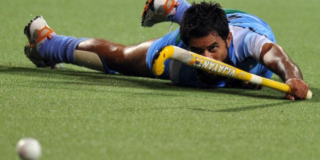 Gurbaj Singh of India watches the ball as he slips on the ground against Malaysia during the field hockey...