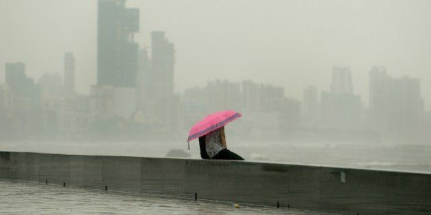 An Indian couple sit at the sea front during rain showers in Mumbai on July 2, 2014. Rain fall helped...