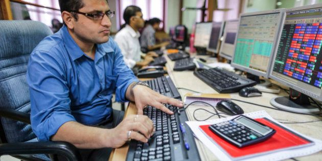 Employees use desktop computers as they monitor data at a securities brokerage in Mumbai, India, on Tuesday,...