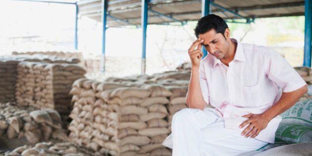 Stressed man sitting on a stack of sacks in warehouse, Anaj Mandi, Sohna, Gurgaon, Haryana,