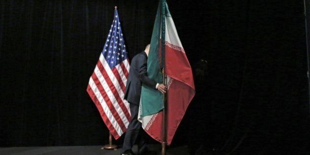 A staff removes the Iranian flag from the stage after a group picture with foreign ministers and representatives...
