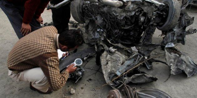 Indian police officers examine the wreckage of a car destroyed in an explosion in Bijbehara town, some...