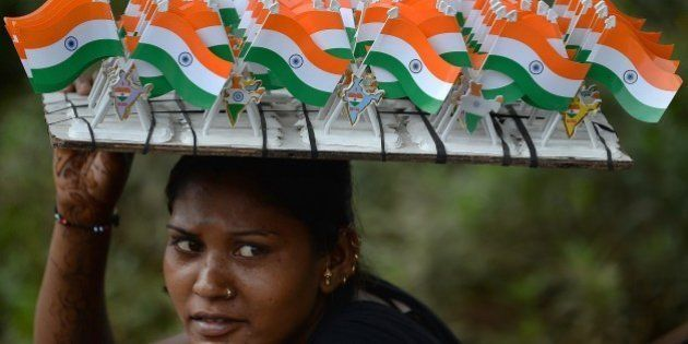 An Indian woman selling miniature Indian tricolour flags waits for customers at the corner of a busy...