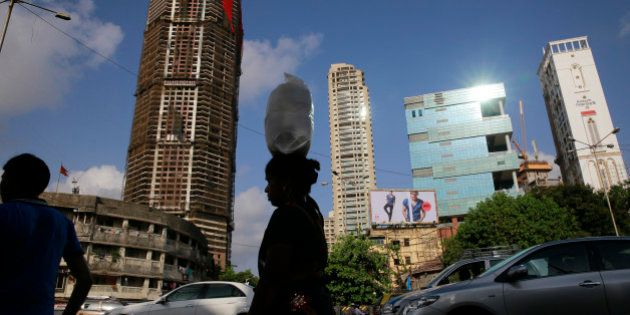 An Indian woman carrying a sack of wheat crosses under construction buildings in Mumbai, India, Tuesday,...
